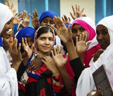 photo of Malala surrounded by girls with their hands raised