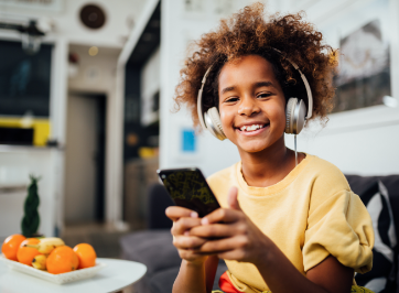 school-age child on device with headphones