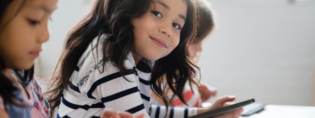 Young girl on device looking sideways at camera and smiling