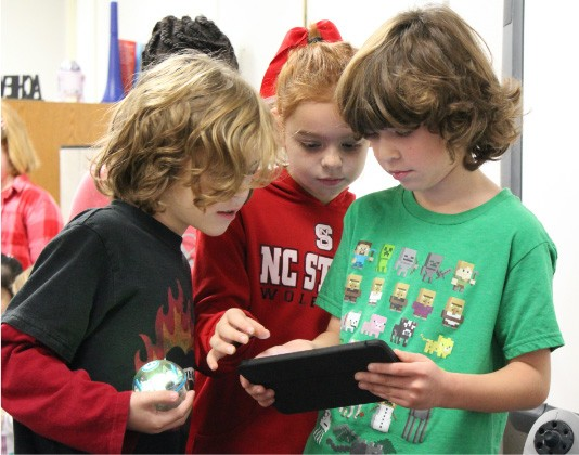 Three young kids working together using device and robot