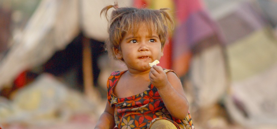 Very young girl in a flowered shirt holding food in her hand